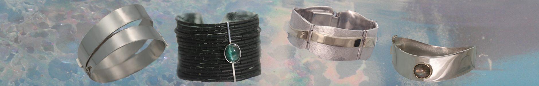 """De armbanden op deze foto zijn in opdracht gemaakt of verkocht uit de collectie: Een strakke zilveren armband, geinspireerd op het bijbelse verhaal, """"de brede smalle weg"""". Een armband van serpentijn kralen en een chrysoberylkattenoog. Een zilveren armband met een gouden strip, symbool voor vijf kinderen, ieder anders, maar wel verbonden. Een glanzende zilveren armband met een labradoriet."""