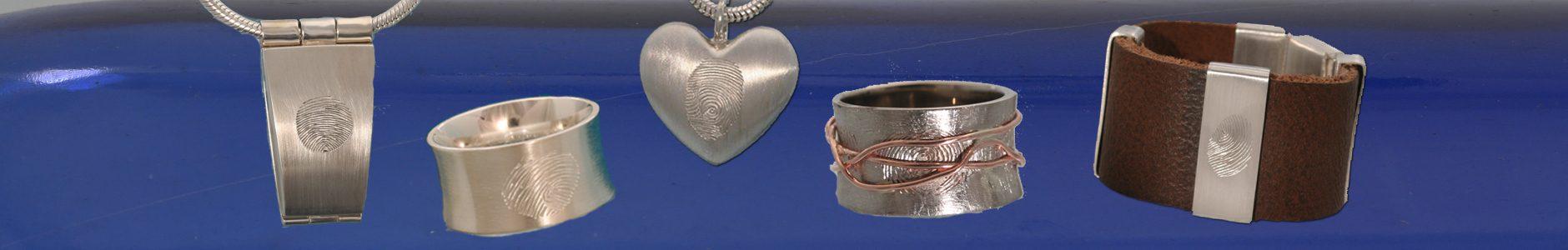 Last Touch.Een medaillon met een vingerafdruk, een ring met een vingerafdruk, een wikkelring met onder de roodgouden draad een vingerafdruk en een lederen armband met een zilveren lus, met hierop een vingerafdruk