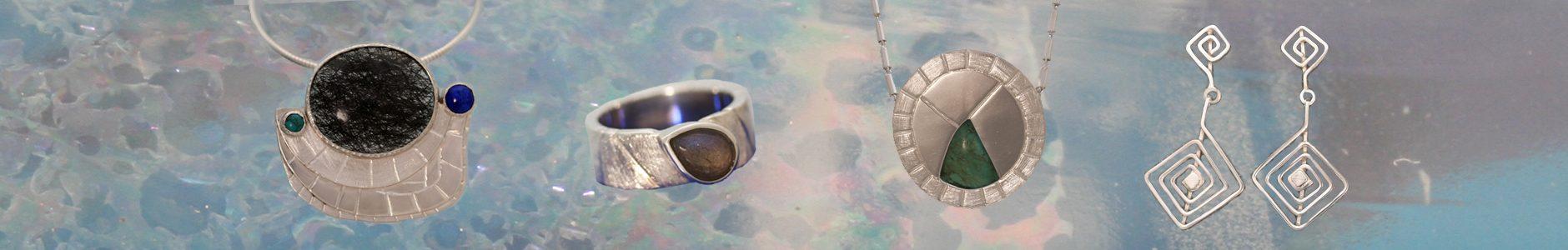 Een hanger met toermalijnkwarts, turkooid en lapis lazuli, een ring met een druppelvormige labradoriet, een hanger met turkoois en lange zilveren oorhangers met doolhoven.